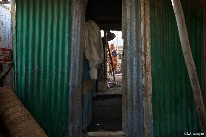 منزل من الصفائح المعدنية (الچينكو) لا يتيسر للكثيرين من سكان القبائل الرحل، ولارتفاع درجة الحرارة فالعائلة تجلس خارجه طوال النهار - قرية لاك عسل